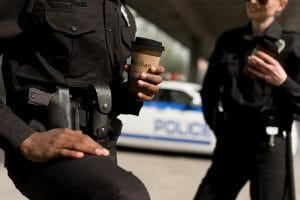 Police holding a cup of Ellianos Coffee - National Coffee with a Cop Day